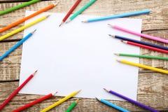 Zeichnende bunte Bleistifte mit Blatt Papier leeres Papier auf Braun flehen an Lizenzfreie Stockfotos