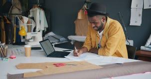 Zeichnende Kleidung des männlichen Modedesigners unter Verwendung des Laptops, der modernes Kleid herstellt stock footage