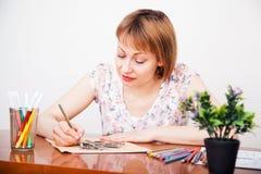 Zeichnung der jungen Frau am Schreibtisch Lizenzfreie Stockfotos