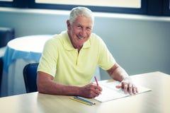 Zeichnung des älteren Mannes mit einem farbigen Bleistift im Zeichnungsbuch lizenzfreies stockbild