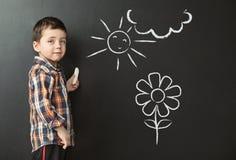 Zeichnung des kleinen Jungen auf der Tafel Stockbilder