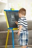 Zeichnung des kleinen Jungen auf Tafel Stockbild