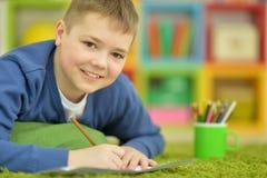 Zeichnung des kleinen Jungen mit Bleistift Lizenzfreies Stockfoto