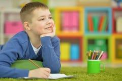 Zeichnung des kleinen Jungen mit Bleistift Stockfotografie