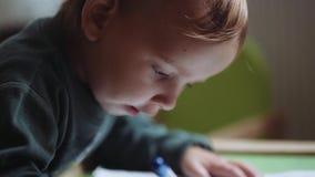 Zeichnung des kleinen Jungen mit Bleistiften auf dem Papier stock footage