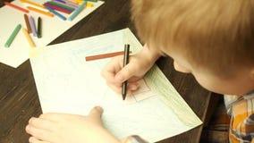 Zeichnung des kleinen Jungen mit farbigen Bleistiften stock footage