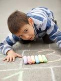 Zeichnung des kleinen Jungen mit Kreide draußen Stockfoto