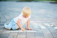 Zeichnung des kleinen Jungen mit Kreiden auf Asphalt Lizenzfreie Stockfotos