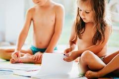 Zeichnung des kleinen Jungen und des Mädchens mit Zeichenstiften Lizenzfreies Stockbild