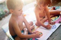 Zeichnung des kleinen Jungen und des Mädchens mit Zeichenstiften Stockbild