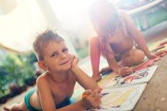 Zeichnung des kleinen Jungen und des Mädchens mit Zeichenstiften Lizenzfreie Stockfotografie