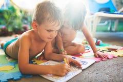 Zeichnung des kleinen Jungen und des Mädchens mit Zeichenstiften Lizenzfreie Stockfotos