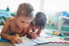 Zeichnung des kleinen Jungen und des Mädchens mit Zeichenstiften stockfotos