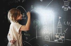 Zeichnung des kleinen Mädchens auf einer Tafel Stockbilder