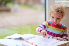 Zeichnung des kleinen Mädchens auf Papier Lizenzfreie Stockfotos