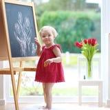 Zeichnung des kleinen Mädchens auf Tafel Stockfoto