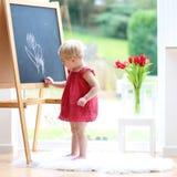 Zeichnung des kleinen Mädchens auf Tafel Stockbilder