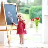 Zeichnung des kleinen Mädchens auf whiteboard Lizenzfreie Stockfotografie