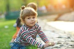 Zeichnung des kleinen Mädchens mit Bürgersteigskreide im Park Stockbilder