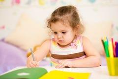 Zeichnung des kleinen Mädchens mit Filzstift Stockfotografie