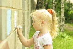 Zeichnung des kleinen Mädchens mit Kreide auf der Wand lizenzfreies stockbild
