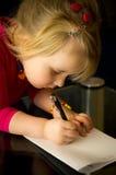 Zeichnung des kleinen Mädchens mit Stift stockfotografie