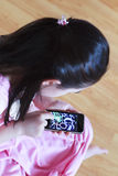 Zeichnung des kleinen Mädchens am Screentelefon Stockbild
