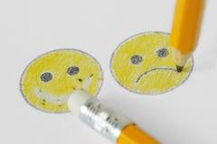 Zeichnung des smileygesichtes mit negativem und positivem Ausdruck mit Bleistift und Gummi - negatives Gefühlkonzept stockfotografie