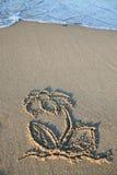 Zeichnung einer Blume als Symbol im Sand eines Strandes Lizenzfreie Stockfotografie