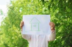 Zeichnung eines grünen Hauses in den Händen eines Kindes Lizenzfreie Stockfotos