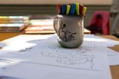 Zeichnung und Becher mit farbigen Bleistiften Lizenzfreie Stockfotografie