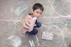 Zeichnung und Farbton des kleinen Jungen durch Kreide auf dem Boden Stockbilder