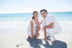 Zeichnungs-Herzform des glücklichen Paars im Sand Stockbild