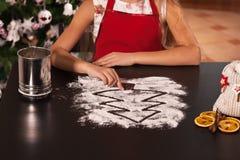 Zeichnungs-Weihnachtsbaum des jungen Mädchens im Mehl zugebereitet, um zu machen Lizenzfreie Stockfotos
