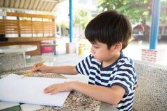 Zeichnungsbild des kleinen Jungen auf Tabelle Stockbilder
