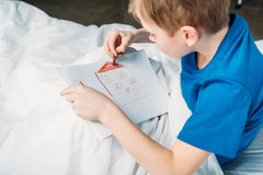 Zeichnungsbild des kleinen Jungen beim Lügen im Krankenhausbett Lizenzfreie Stockfotos