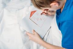 Zeichnungsbild des kleinen Jungen beim Lügen im Krankenhausbett Stockbild