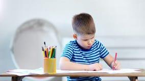 Zeichnungsbild des kleinen Jungen des mittleren Schusses überzeugtes auf Papier unter Verwendung der farbigen Bleistifte, die auf stock video