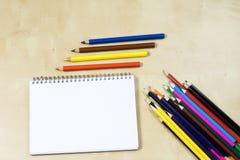 Zeichnungsbleistifte und ein skizzierendes Notizbuch auf einem Holztisch Sket Stockbild