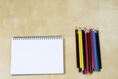 Zeichnungsbleistifte und ein skizzierendes Notizbuch auf einem Holztisch Sket Stockbilder