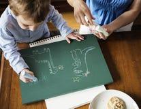 Zeichnungsdinosaurier des kleinen Jungen mit Kreide Stockfotografie