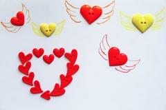 Zeichnungsflügel auf vielen Herzformknöpfen vereinbart lizenzfreies stockbild