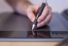 Zeichnungshand auf der Tablette stockfotografie