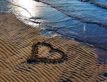 Zeichnungsherz auf dem Sand auf dem Strand Stockfoto