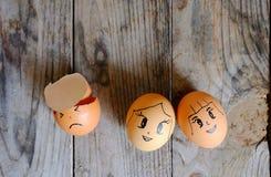 Zeichnungskarikatur auf drei Eiern mit Wassertropfen legen auf einen Holztisch, Fokus auf Eiern stockfotos