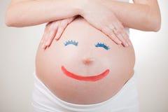 Zeichnungspersonen auf schwangerem Bauch Stockfotos