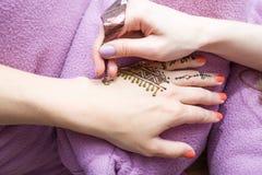 Zeichnungsprozeß von Hennastrauch menhdi Verzierung auf der Hand der Frau Makrodetail des kosmetischen Behälters voll echter Perl Stockfotos