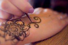 Zeichnungsprozeß von Hennastrauch menhdi Verzierung auf der Hand der Frau Makrodetail des kosmetischen Behälters voll echter Perl Lizenzfreies Stockfoto