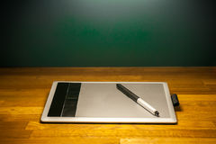 Zeichnungstablette und -stift auf hölzerner Schreibtischtabelle Lizenzfreie Stockfotos