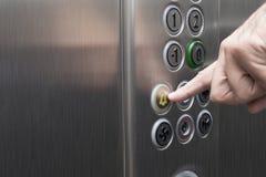 Zeigefinger, der den Warnungsknopf im Aufzug drückt lizenzfreies stockfoto